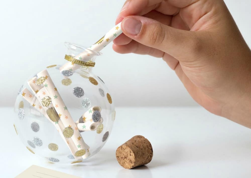 hand putting notes in baby keepsake ornament
