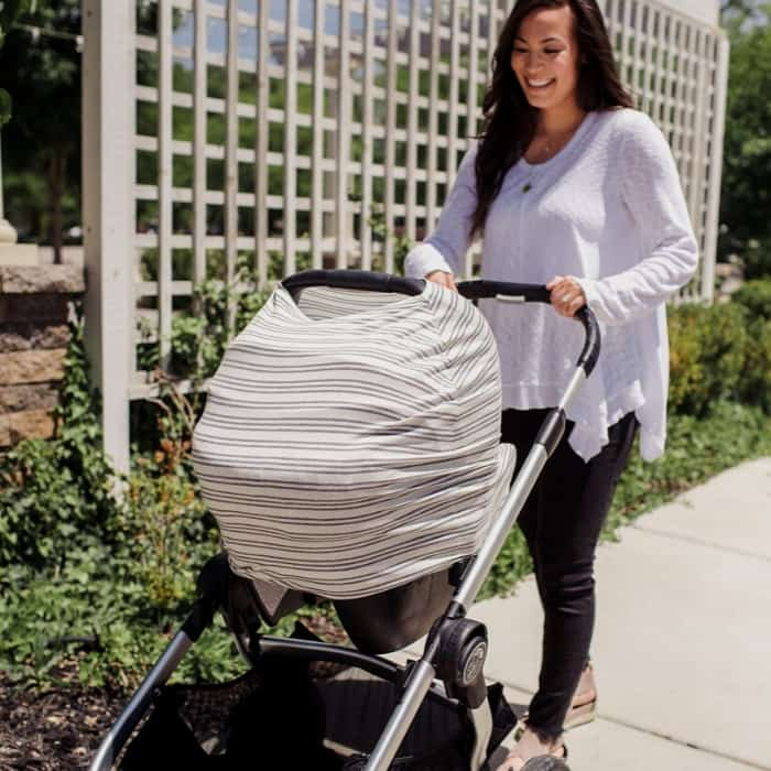 woman pushing baby stroller with car seat cover
