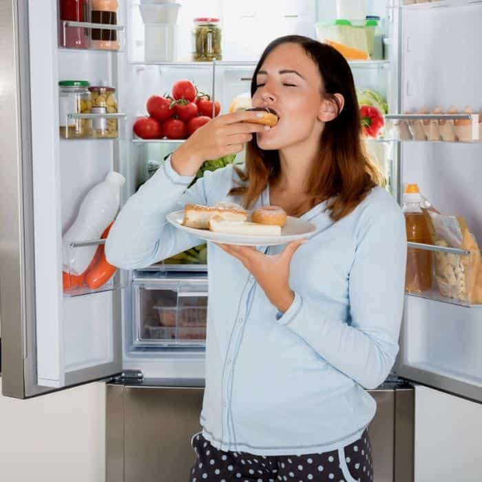 newly pregnant woman eating food in front of open fridge