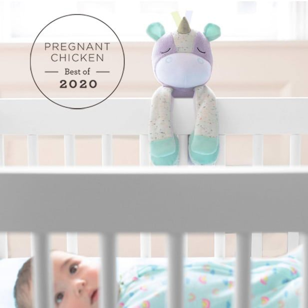 unicorn soother clipped onto the side of a white baby crib