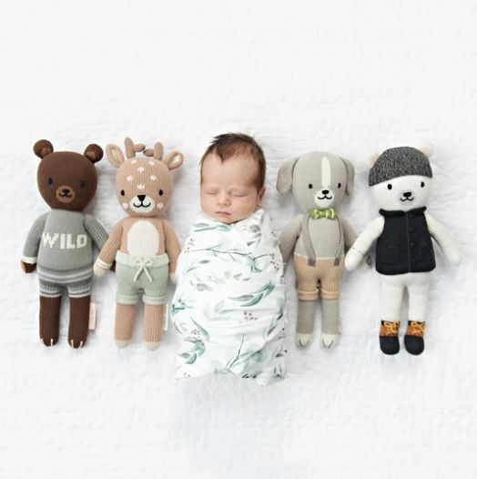 baby swaddled between four cuddle and kind hand knit dolls