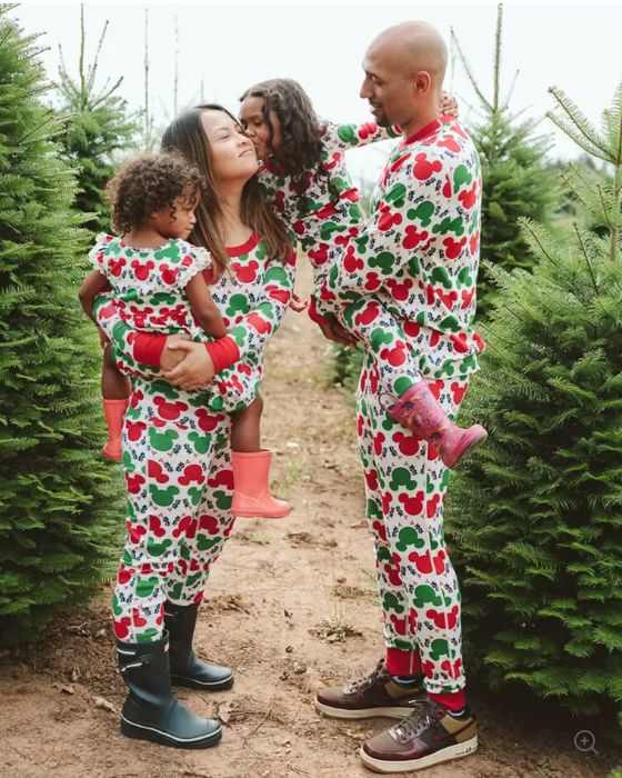 A family standing in a row of Christmas trees wearing matching pajamas featuring green and red Mickey Mouse heads.