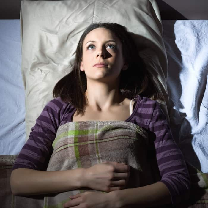 woman waking up in bed after an intense dream