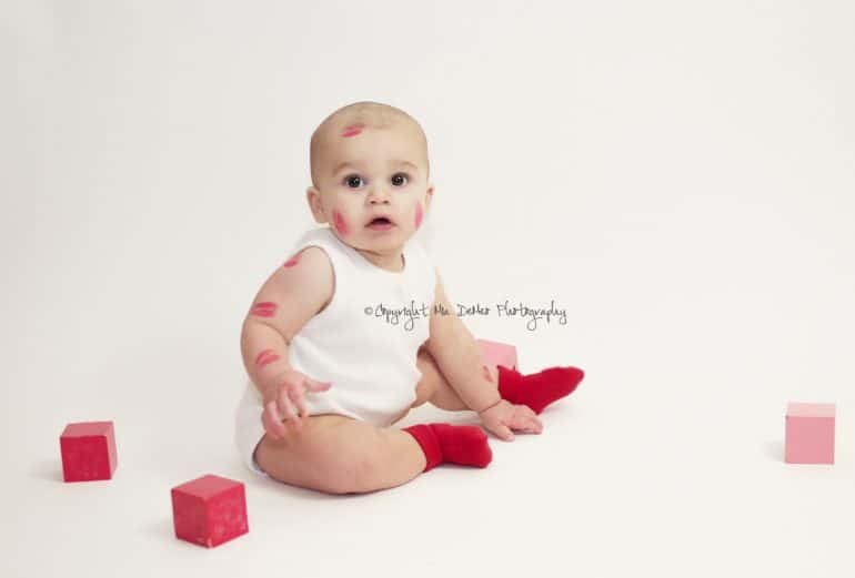 Baby sitting on floor with pink on red blocks and kiss marks on their face and arms - Baby's First Valentine's Day Photo shoot