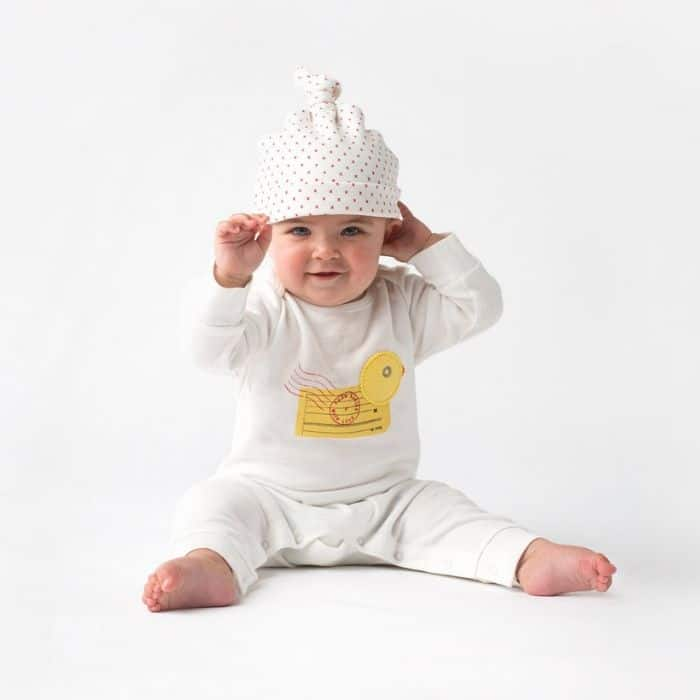 Baby wearing soft white organic outfit from Babies With Love