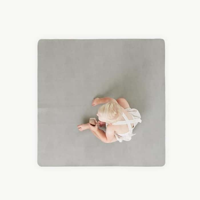 child sitting on gray gathre mat