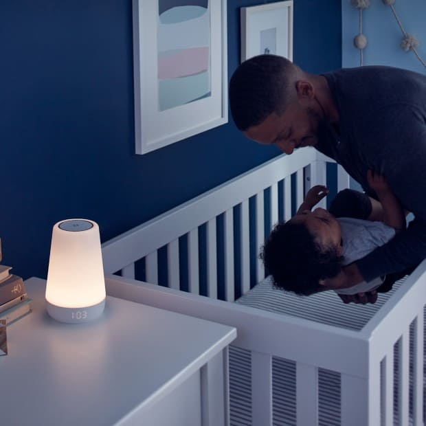 dad putting baby in crib with nightlight on side table at night, Hatch Rest Plus Review