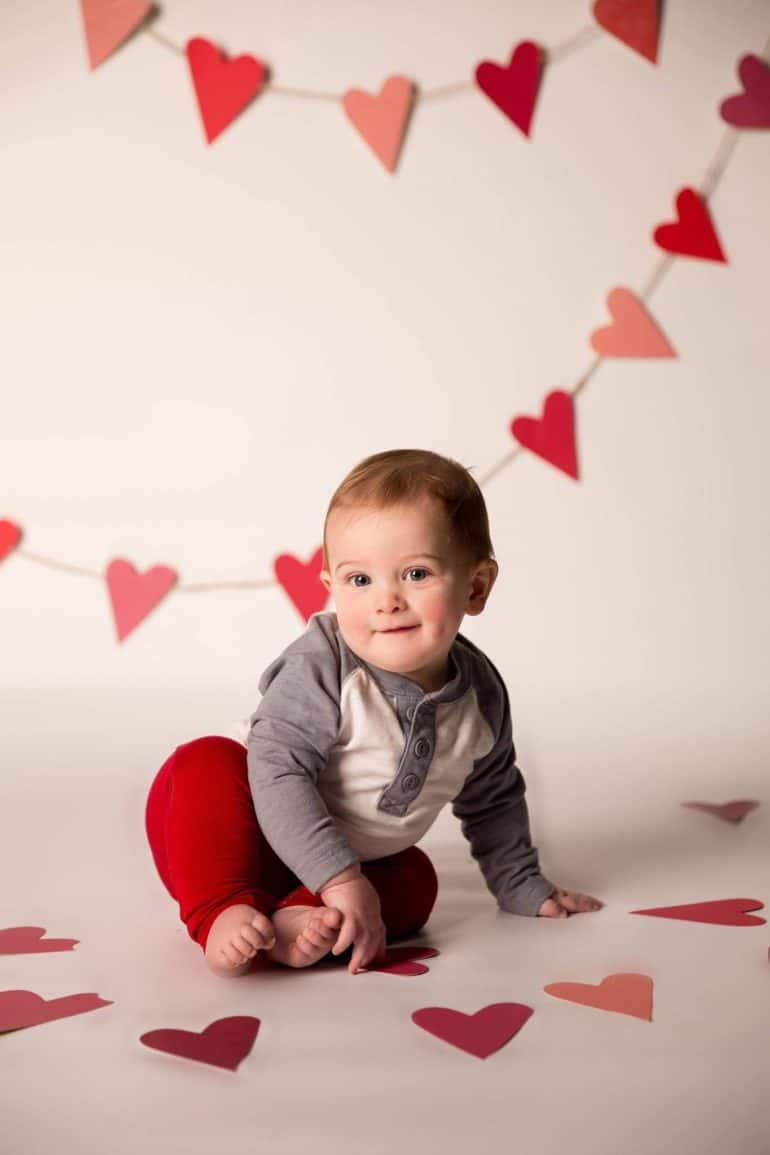 baby sitting on floor surrounded by hearts for Baby's First Valentine's Day Photo shoot