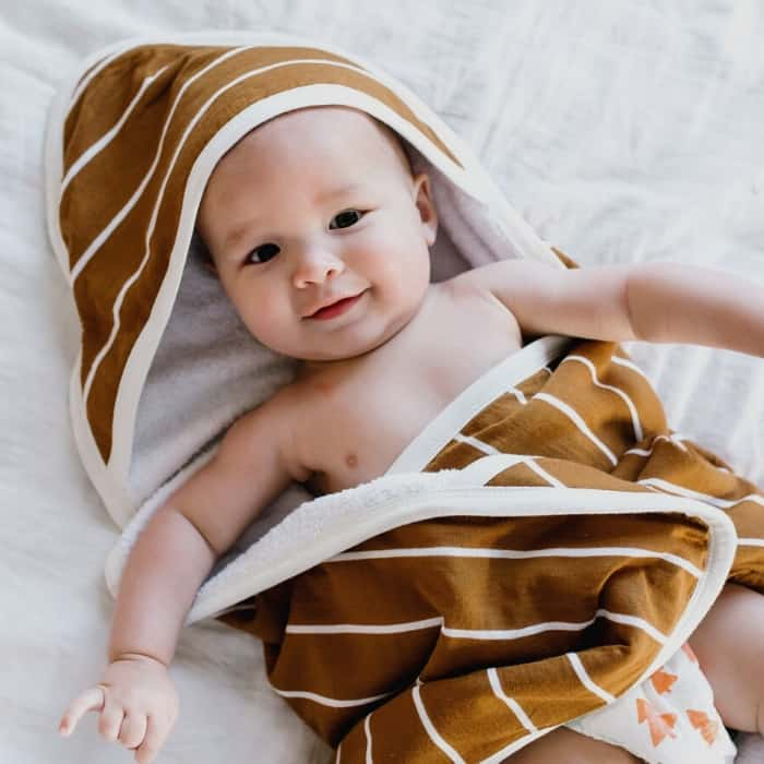 baby with brown and white striped towel