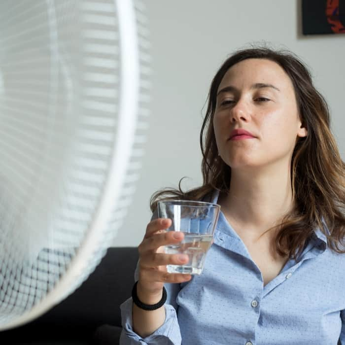 over heated woman drinking water due to early pregnancy symptoms