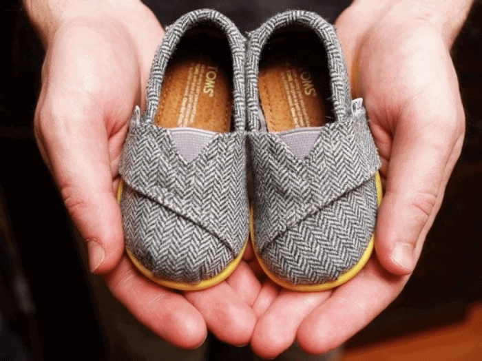 hands holding a pair of baby sized Toms shoes