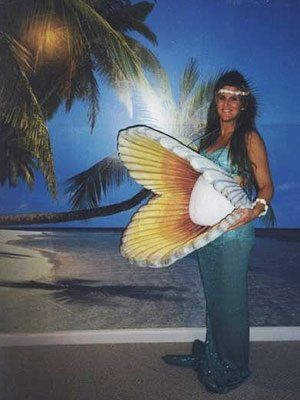 Pregnant woman dressed as mermaid with pearl belly