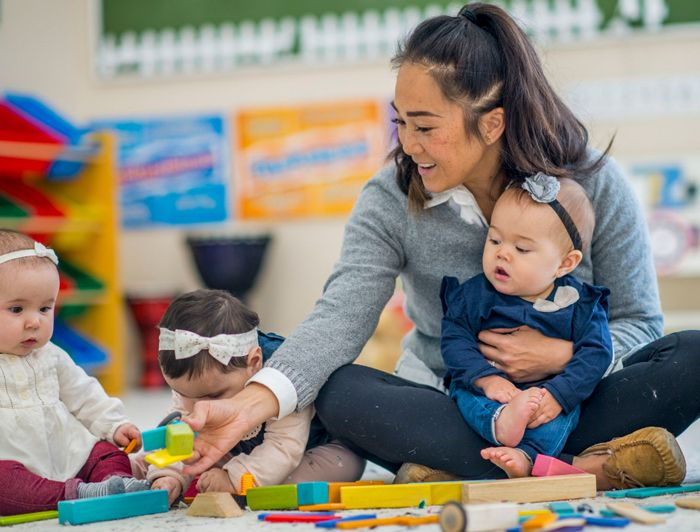 woman in her home daycare holding a baby on her lap