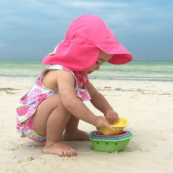 baby playing at the beach wearing a pink sun hat