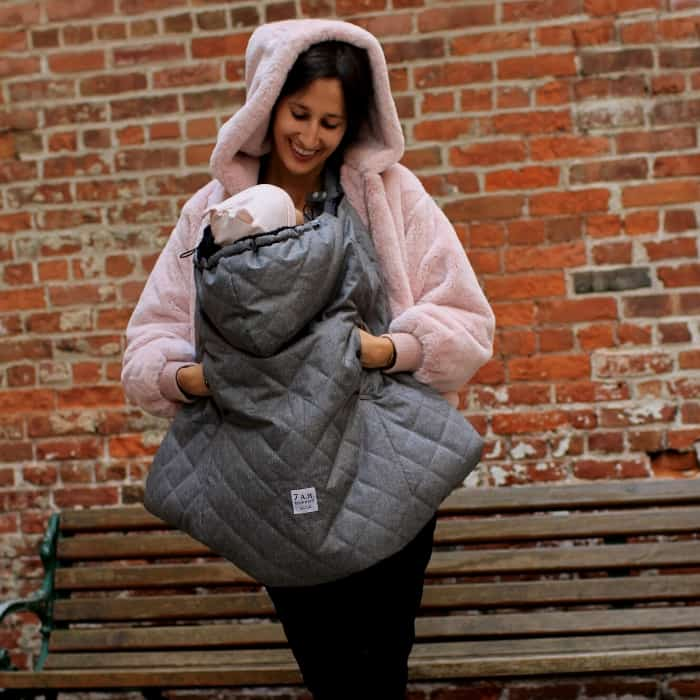 woman outside carrying baby with a carrier cover