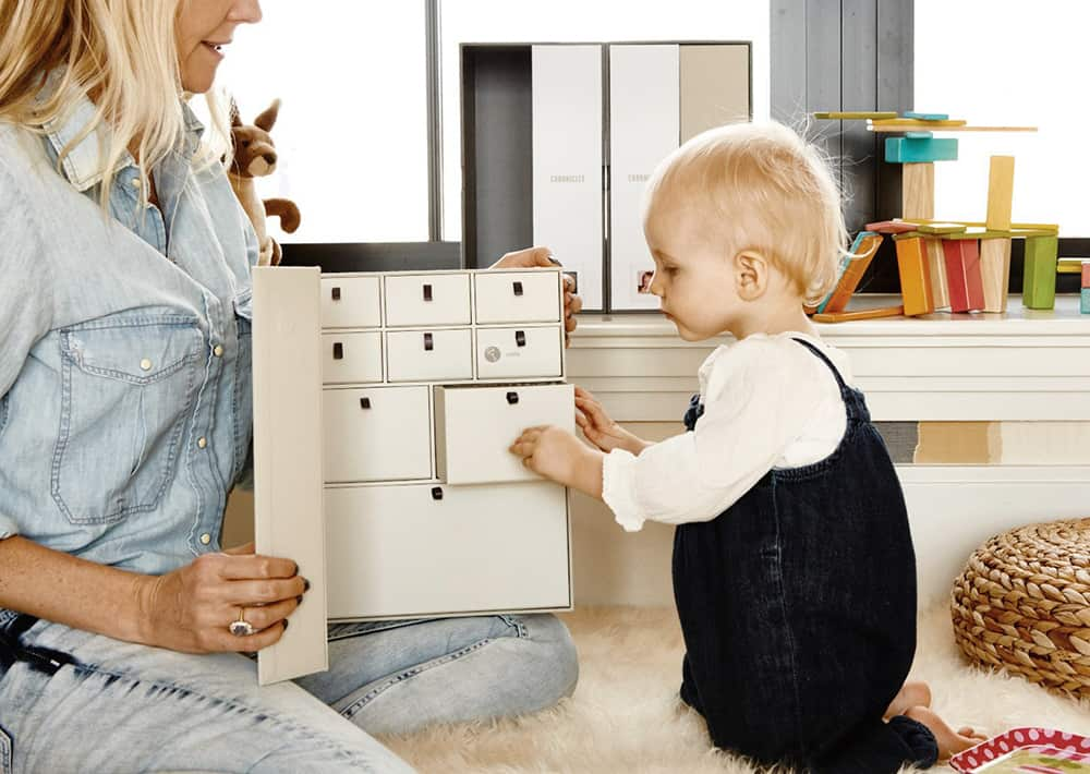 mom and baby putting items in memory box