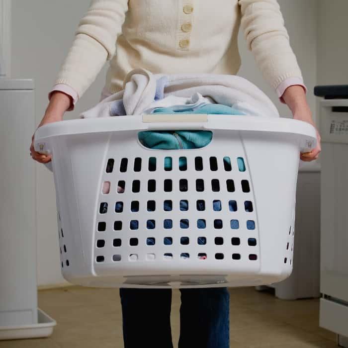 woman holding basket full of laundry