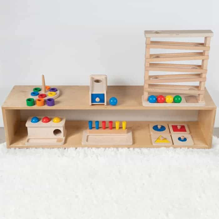 Montessori play room with a low shelf with wooden toys