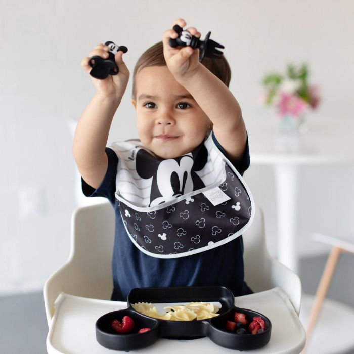 Toddler sitting in a highchair wearing Mickey Mouse bib, eating off Mickey Mouse plate, playing with Mickey Mouse utensils.