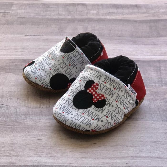 """Tiny cloth moccasins made from fabric that says """"Minnie Mouse"""" with small Minnie Mouse head."""