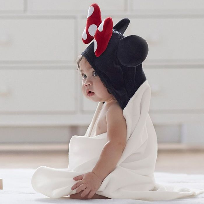 Baby sitting wrapped up in Minnie Mouse hooded towel