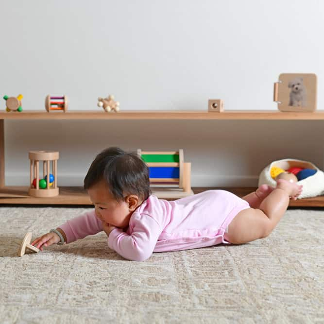 baby playing with a wooden toy in a Montessori play room
