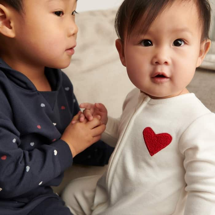 two kids holding hands dressed in heart sleepers