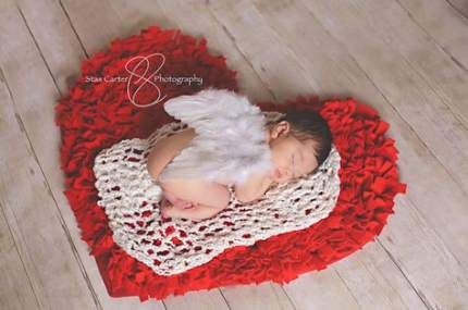 Newborn sleeping on red heart rug with angel wings on their back