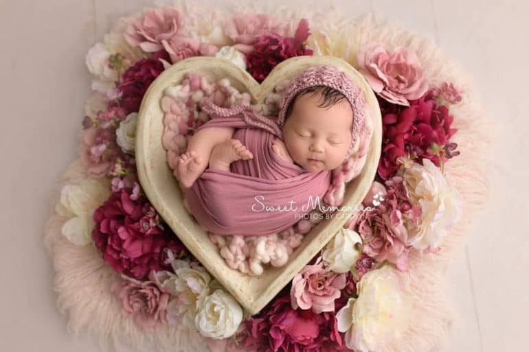 Swaddled newborn sleeping in heart shaped basket surrounded by flowers - Baby's First Valentine's Day Photo shoot