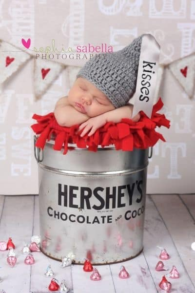 Baby sleeping in Hershey's tin with a gray knitted hat - Baby's First Valentine's Day Photo shoot