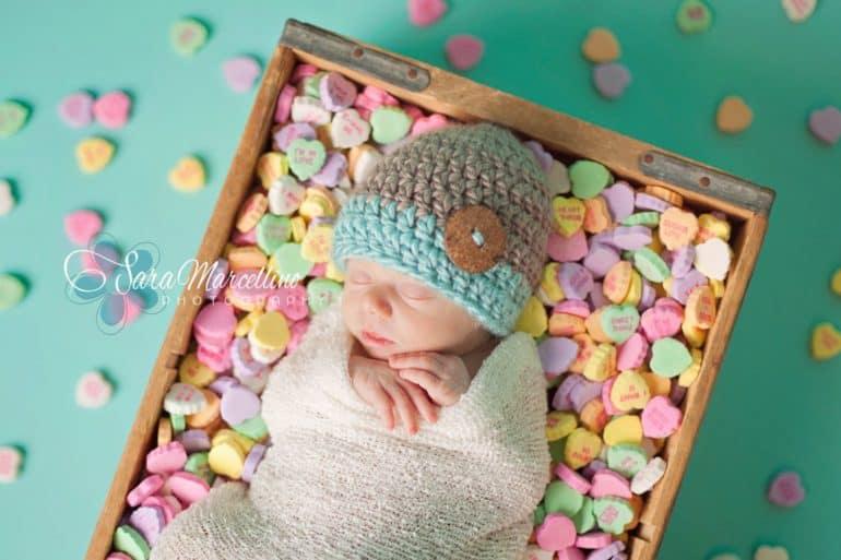 Newborn sleeping in box of Sweat Hearts