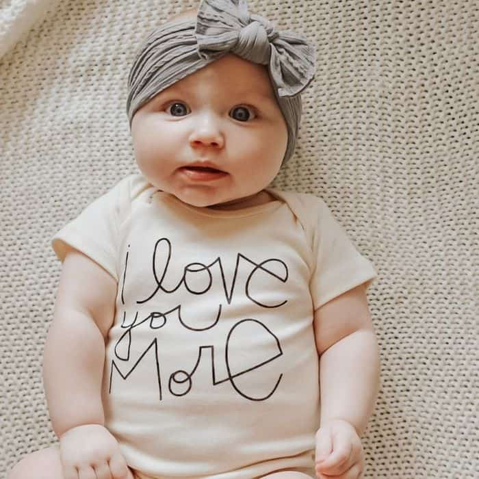 Baby with bow wearing an 'I love you more' onesie