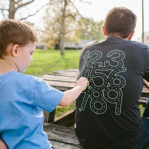 child using car to trace numbers on his dad's T-shirt - father's day gift