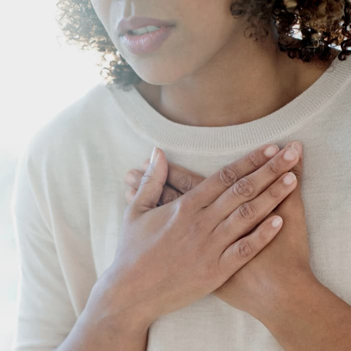 woman holding her chest with a shortness of breath