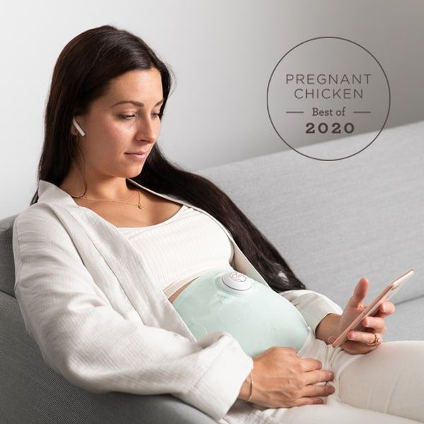 pregnant woman sitting on couch looking at her app while wearing an Owlet Belly Monitor
