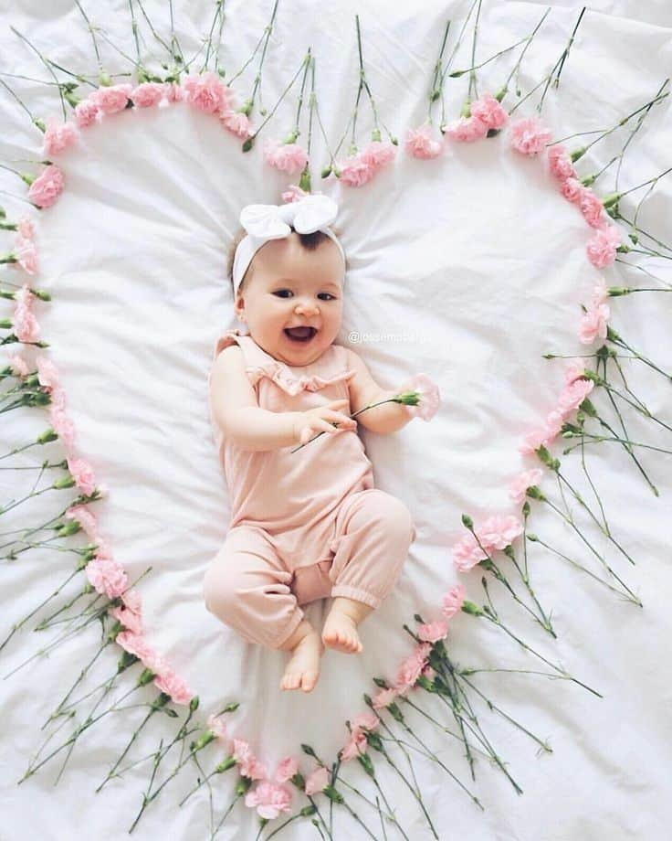 Laughing baby laying on bed surrounded by pink carnations