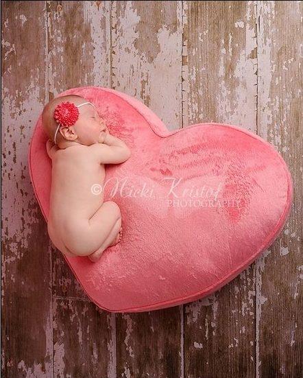 Newborn sleeping on pink fuzzy heart pillow with flower headband on