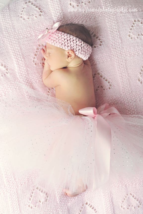 Baby sleeping on soft pink blanket with pink tutu and pink headband