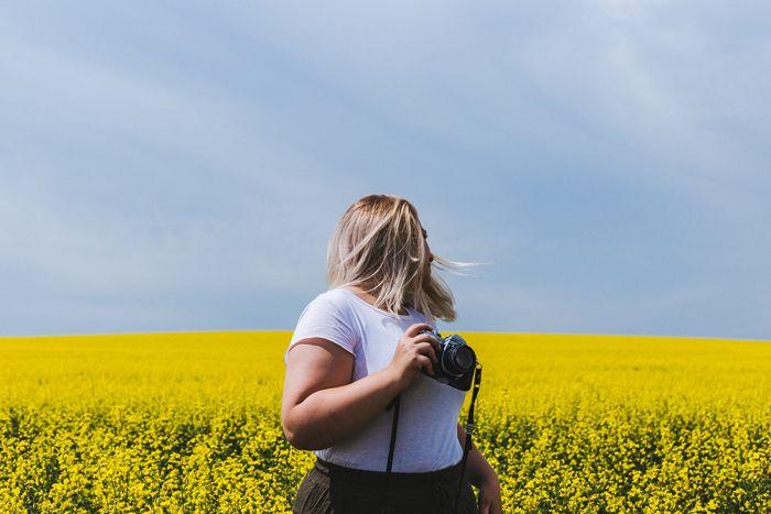photographer in a field of yellow flowers