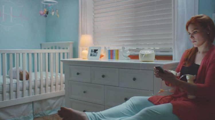 mom pumping breastmilk at night looking at phone