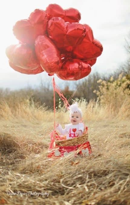 Baby in a field with red heart balloons