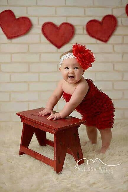 baby standing next to red stool with heart decor for Baby's First Valentine's Day Photo shoot