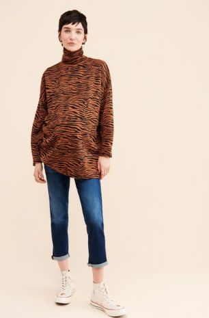 pregnant woman wearing Paige maternity jeans and an animal print turtleneck after she chose to rent maternity clothes