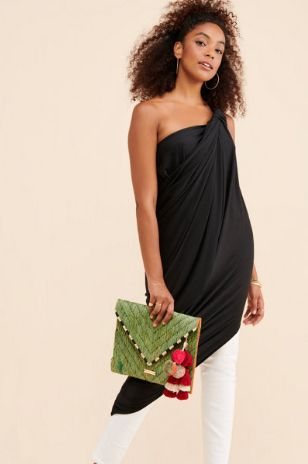 woman wearing black shirt with while leggings holding a clutch purse
