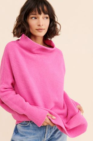 woman wearing bright pink sweater rented from Nuuly