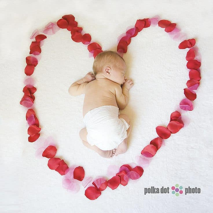 Sleeping newborn laying inside heart made from pink and red rose petals