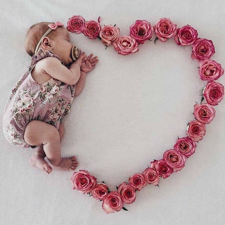 Sleeping baby laying next to heart made out of pink roses