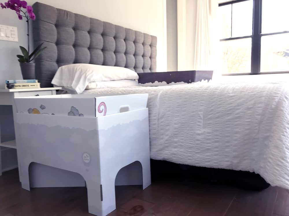 smitten baby box with stand next to bed follows safe sleep guidelines
