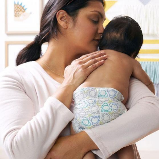 mom holding baby wearing seventh generation diaper