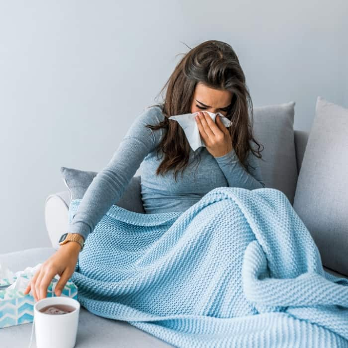 sick woman blowing her nose on the couch